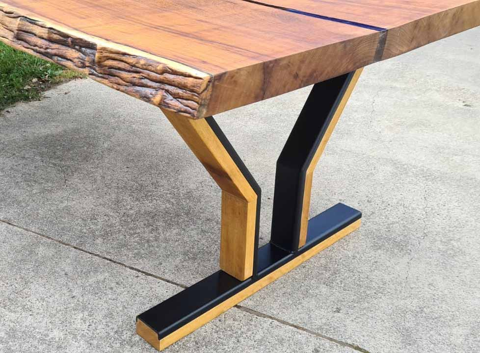 Boomstamtafel van iroko met epoxy en een designonderstel van hout en staal