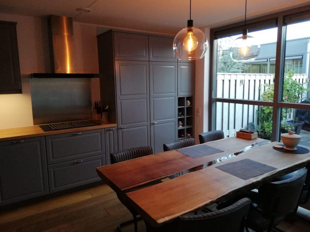 Keuken met daarin een boomstamtafel van iroko met een epoxyrivier